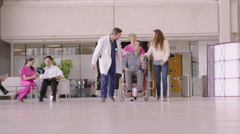 4K Caring medical staff assisting patient in wheelchair in busy modern hospital Stock Footage