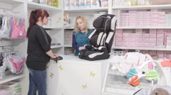 Sales clerk helps the customer to choose infant car seat for baby Stock Footage