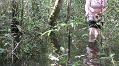Adult Caucasian woman walking trough flooded Amazon jungle Stock Footage