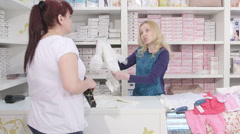 Woman buying white dress for baptism in baby and maternity shop Stock Footage