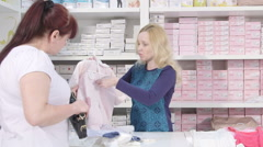 Sales clerk helps a woman to choose clothes for the baby in maternity shop Stock Footage