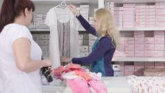 Woman looking for clothes for pregnant nursing mothers in baby maternity shop Stock Footage