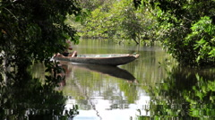 Indigenous adult man navigating in Amazonian jungle in wooden canoe - stock footage