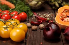 an abundance of vegetables and spices closeup on wooden table tomatoes, pumpkins - stock photo