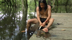 Indigenous man cleaning a fish in Amazonian jungle of Ecuador Stock Footage