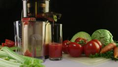 Dolly: Making fresh vegetable juice from tomato using masticating juicer machine - stock footage