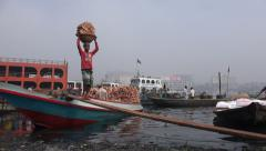 Carrying baskets with heavy bricks from a boat in Dhaka, Bangladesh Stock Footage