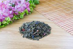 Blend of green tea on a table with colours2. - stock photo