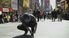 Guy ties his shoes Times Square man tying sneakers midtown Manhattan slow 4K NYC Stock Footage