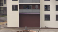 Workers with helmets clean window in new build residential house Stock Footage