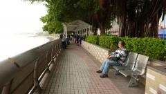 People resting in covered sea-front promenade at daytime, Tuen Mun town Stock Footage