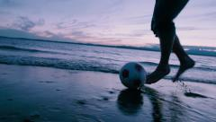Man Dribbling Soccer ball in Front of Waves at Sunset - stock footage