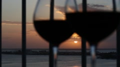 Two glasses with red wine on balcony overlooking at sunset Stock Footage