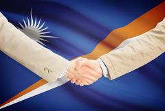 Stock Illustration of Businessmen shaking hands with flag on background - Marshall Islands