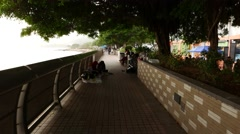 Walking through Tuen Mun promenade, people resting at sea-front park Stock Footage