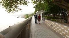 People on seaside promenade, Tuen Mun seafront, public green alley Stock Footage