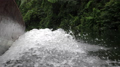 Water level shot of water being sprayed by powerful speedboat in Amazon jungle Stock Footage