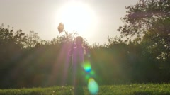 Little girl playing with windmill in sunny spells Stock Footage