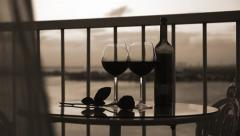 Two glasses and bottle with red wine on balcony Stock Footage