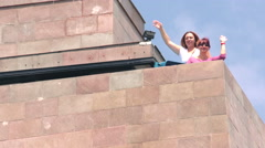 Two best friends waving their hands from the top of Center of the World monument Stock Footage