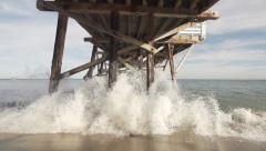 Slow Motion Wave Crashing Under Pier. Stock Footage