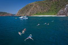 Unidentified tourists enjoying a daytrip snorkeling in beautiful paradise beach Stock Photos