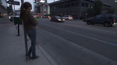 Girl Leans on Post Using Smart Phone Mobile in Downtown with Green Screen. Stock Footage