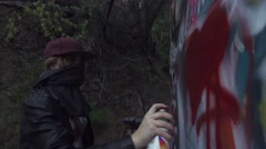 Girl Spray Painting Graffiti on Wall in Slow Motion. Stock Footage