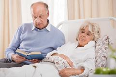 Husband reading ill wife book - stock photo