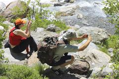 Group of tourists making a snap shot on the mountain river Stock Photos