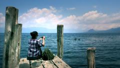 Tourist sitting on pier Stock Footage
