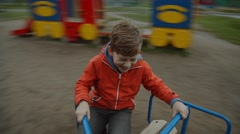 Emotional boy spinning on the carousel, smile and laugh Stock Footage