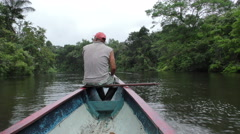 Ranger in Cuyabeno on the bow of the canoe looking for potential wildlife Stock Footage