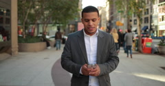 Young African American black Latino man in city walking texting cell phone Stock Footage