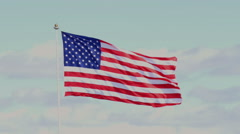 The American flag waving in blue sky - stock footage