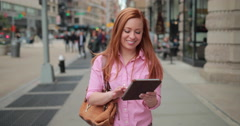 Young caucasian woman in city walking using tablet pc Stock Footage