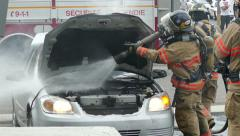 Firemen putting out a car fire by spraying water under the hood - Commercial Stock Footage