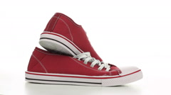 Red sneakers revolve on a white background Stock Footage