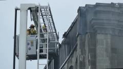 Fireman tearing up apart pieces of a of building on fire - Commercial licensing Stock Footage
