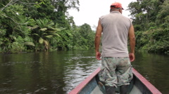 Cuyabeno Wildlife Reserve ranger riding in front of a motorized canoe to spot Stock Footage