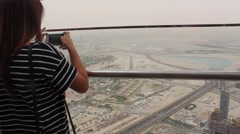 Woman takes photos of Dubai from above Stock Footage