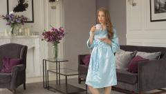 Attractive young woman in a blue robe is drinking from a cup at her home. Stock Footage