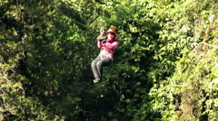 Zip line slow motion tracking shot of an adult tourist woman Stock Footage