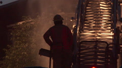 Fire fighter standing next to lit up ladder on firetruck - Commercial licensing Stock Footage