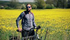 Young, handsome man with a bike admire a rape seed field HD Stock Footage