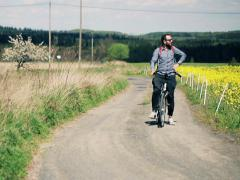 Young, handsome man on a bike admire country road NTSC - stock footage
