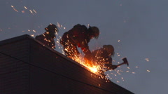 Firemen using saw at night and creating sparkling ambers - Commercial licensing Stock Footage