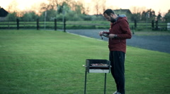 Young man take a picture of a meat on the grill in the garden HD Stock Footage
