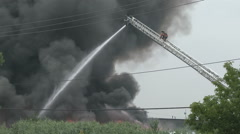 Fire fighter climbing ladder with huge cloud of black smoke - Commercial Stock Footage