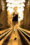 Active female athlete running on railaway tracks. - stock photo